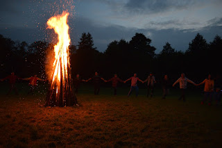 A neatly-made bonfire with a wide circle of people around, hands linked, processing around the bonfire in a clockwise direction.