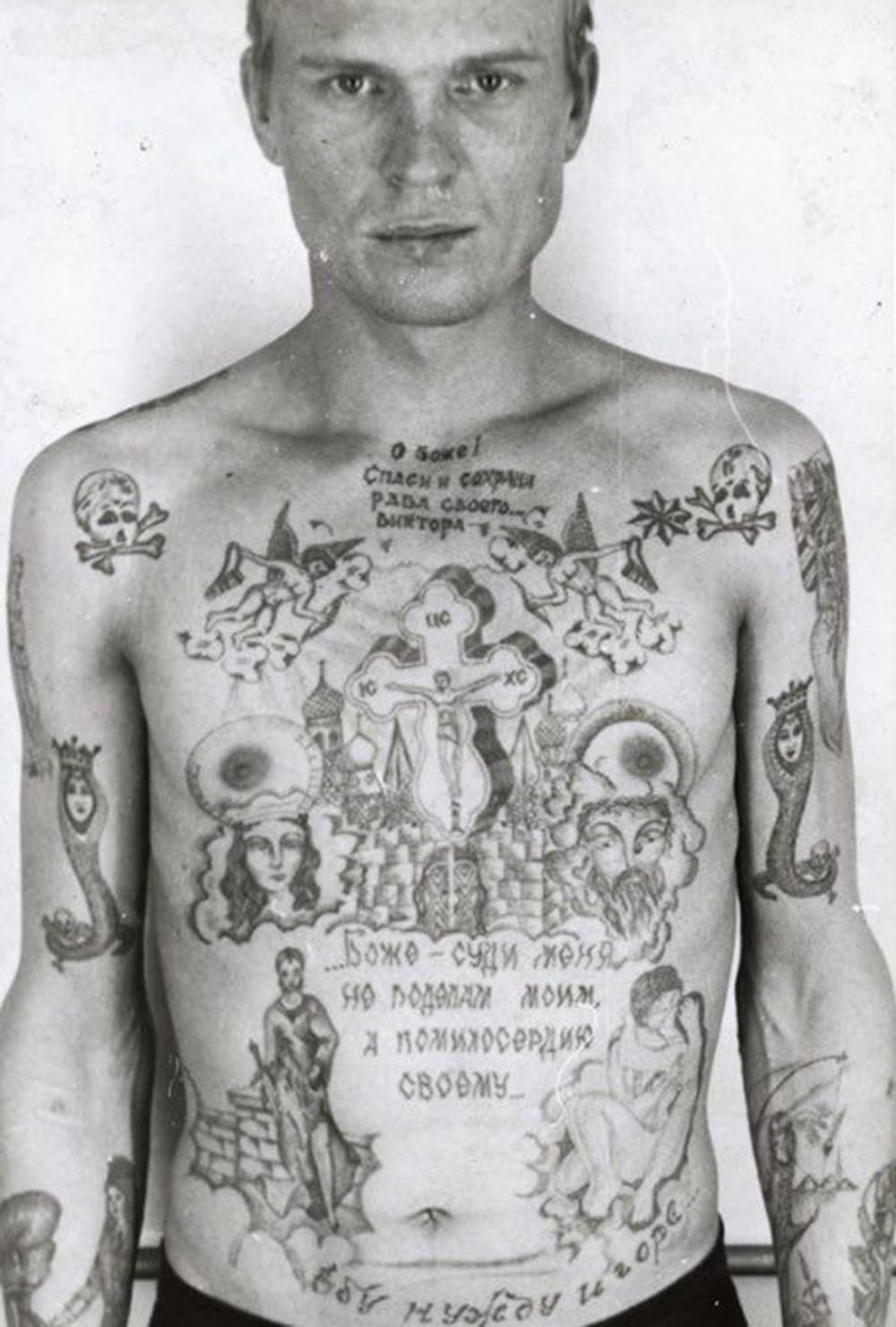 Text above the cross reads 'O Lord, Save and Protect your servant Viktor.' Text beneath reads 'God do not judge me by my deeds but by your mercy.' Text above the waist reads 'I fuck poverty and misfortune.' The skull and crossbones show the prisoner is serving a life term. The single eight-pointed star denotes that he is a 'semi-authority' among thieves. The girl catching her dress with a fishing line on his left forearm is a tattoo worn by hooligans and rapists. The snake coiled around human remains (positioned on the middle third of each arm) is a variation on an old thieves' tattoo. The snake is a symbol of temptation; here the snake's head has been replaced by that of a woman, the temptress. Tattooed on the right side of the stomach is a version of Judith (1504) as painted by Giorgione; this is intended as a symbol of a scheming, seductive woman who betrays a noble man.
