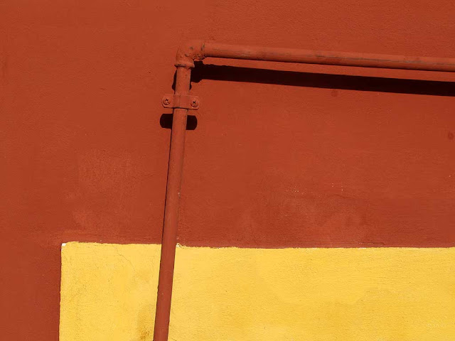 Painted pipe on a red and yellow wall, Livorno