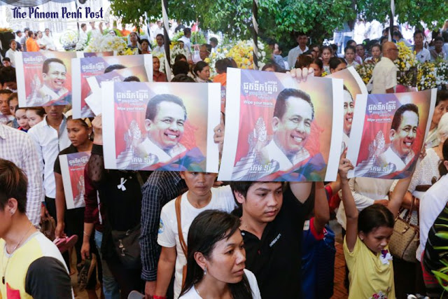 Mourners hold Kem Ley posters at the capital's Wat Chas pagoda earlier this year during the analyst's funeral. Heng Chivoan