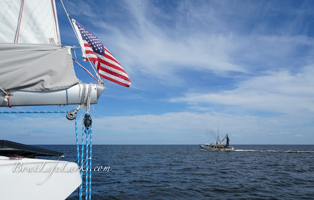 Sailboat with American flag and a fishing boat, Pamlico Sound, North Carolina