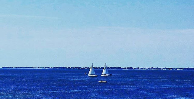 Two boats are sailing in blue water of Odet River