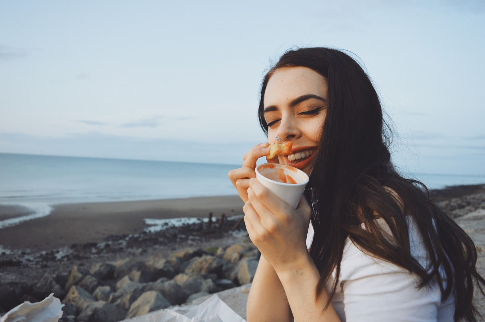 girl eating chips on seafront