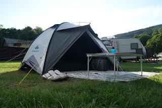 Ein weißes Zelt steht auf einer Wiese. Davor Picknickdecke und Tisch