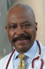 Professional portrait of a middle-aged Black doctor, bald and with a thick moustache. He is wearing a lab coat, tie, and stethescope.