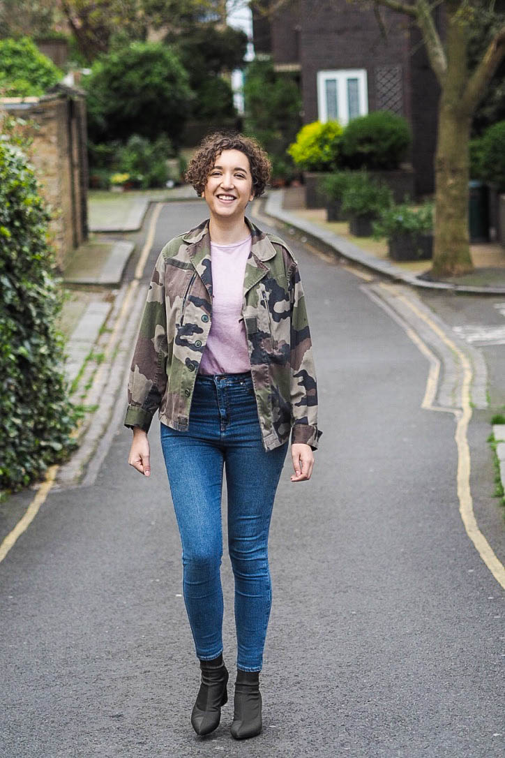 Fashion blogger in camo jacket, pink tshirt, jeans, khaki boots