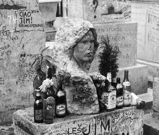 Illusztráció vershez, Jim Morrison párizsi Pére-Lachaise temetőben a sírján álló, összefirkált szobor, sörösüvegekkel és cigarettával dekorálva.