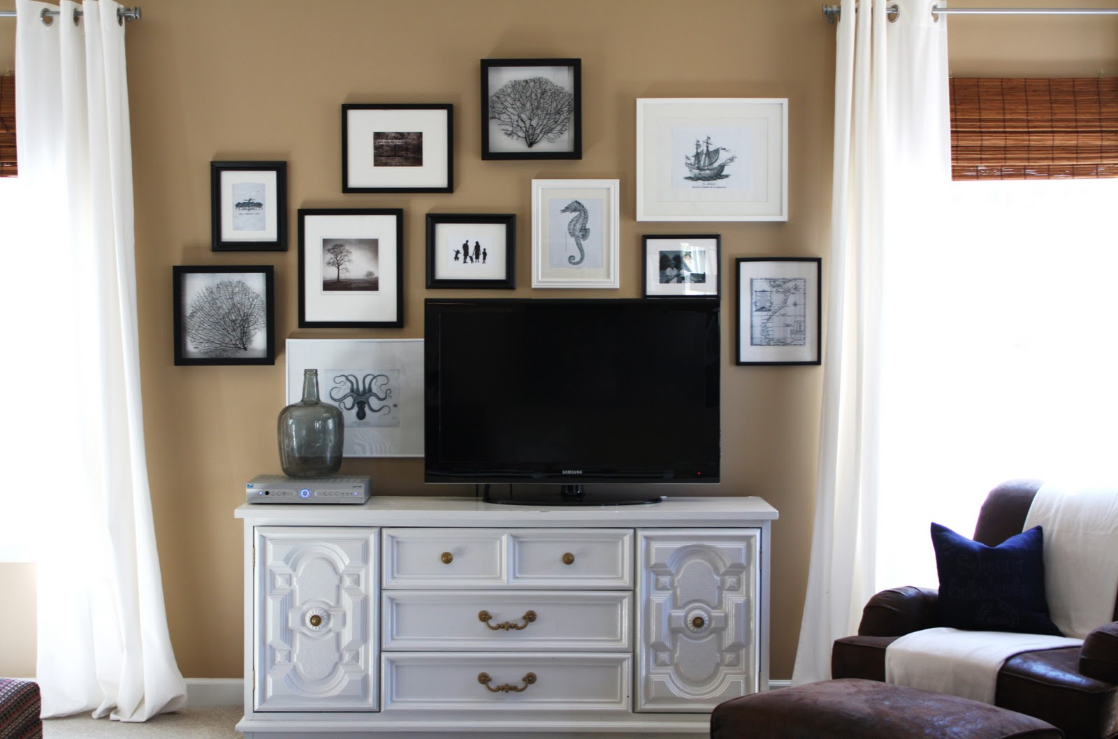 By Using A Grouping Of Black And White Framed Art The Flat Screen Becomes Part