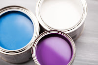Top view of three paint cans, one blue, one purple, and one white.