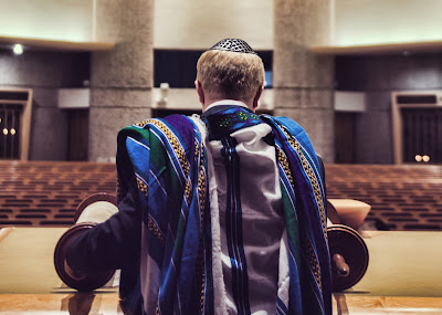 bar mitzvah boy in synagogue with torah scroll