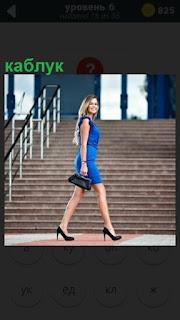 около лестницы проходит девушка в платье на высоких каблуках