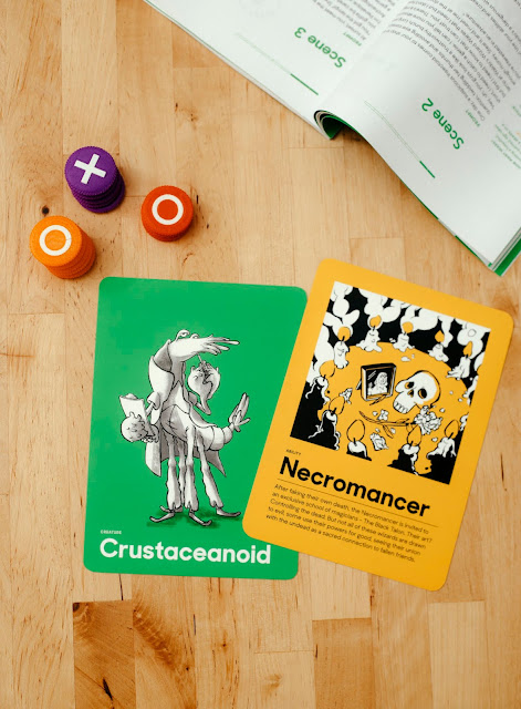 "Two cards, the ""crustaceanoid"" and the ""necromancer"" with three tokens with x's and o's on them next to the rule book."
