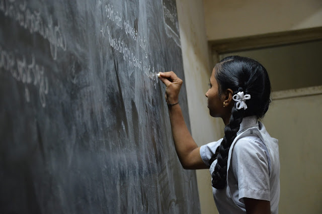 Photo of school girl student writing on board