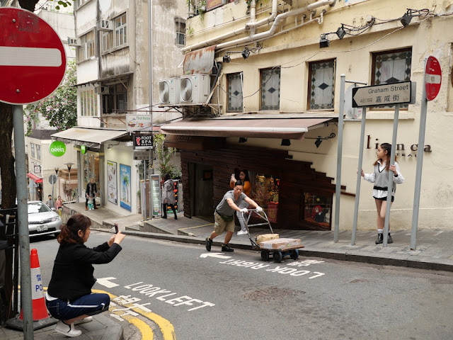 man pushes a cart through the scene as a woman tries to photograph another woman