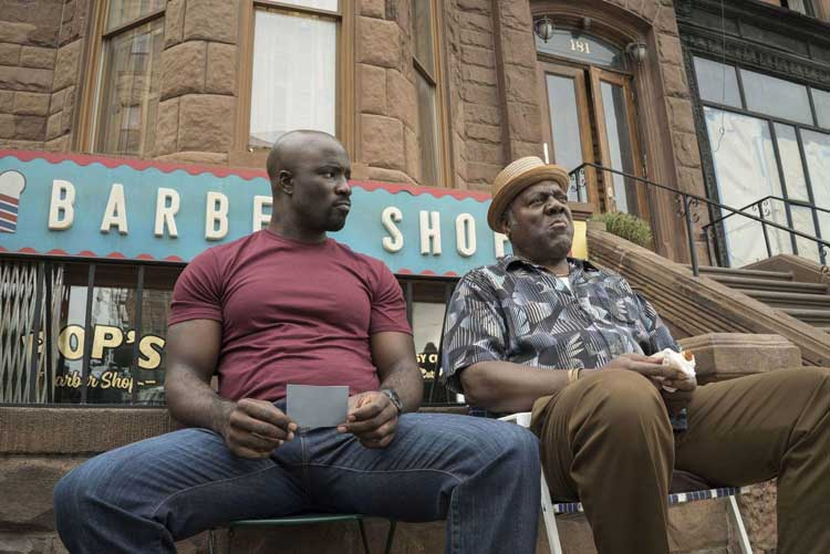 Luke Cage (Mike Colter) and Pop (Frankie Faison) sit outside the barebershop in Luke Cage.