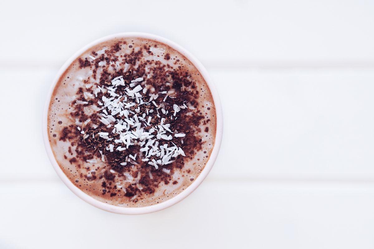 Gorące domowe kakao z dodatkiem bitej śmietany, wiórków kokosowych i tartej, gorzkiej czekolady.