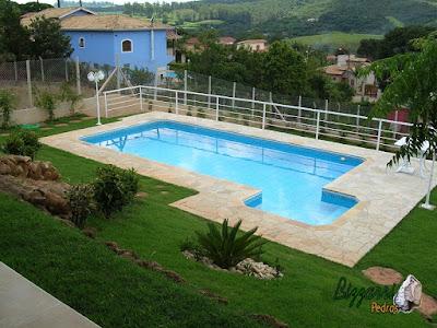Construção de piscina de concreto com o revestimento com pastilhas de vidro, o piso da piscina com pedra São Tomé tipo caco com o peitoril da piscina de alumínio e a execução do gramado com grama esmeralda.