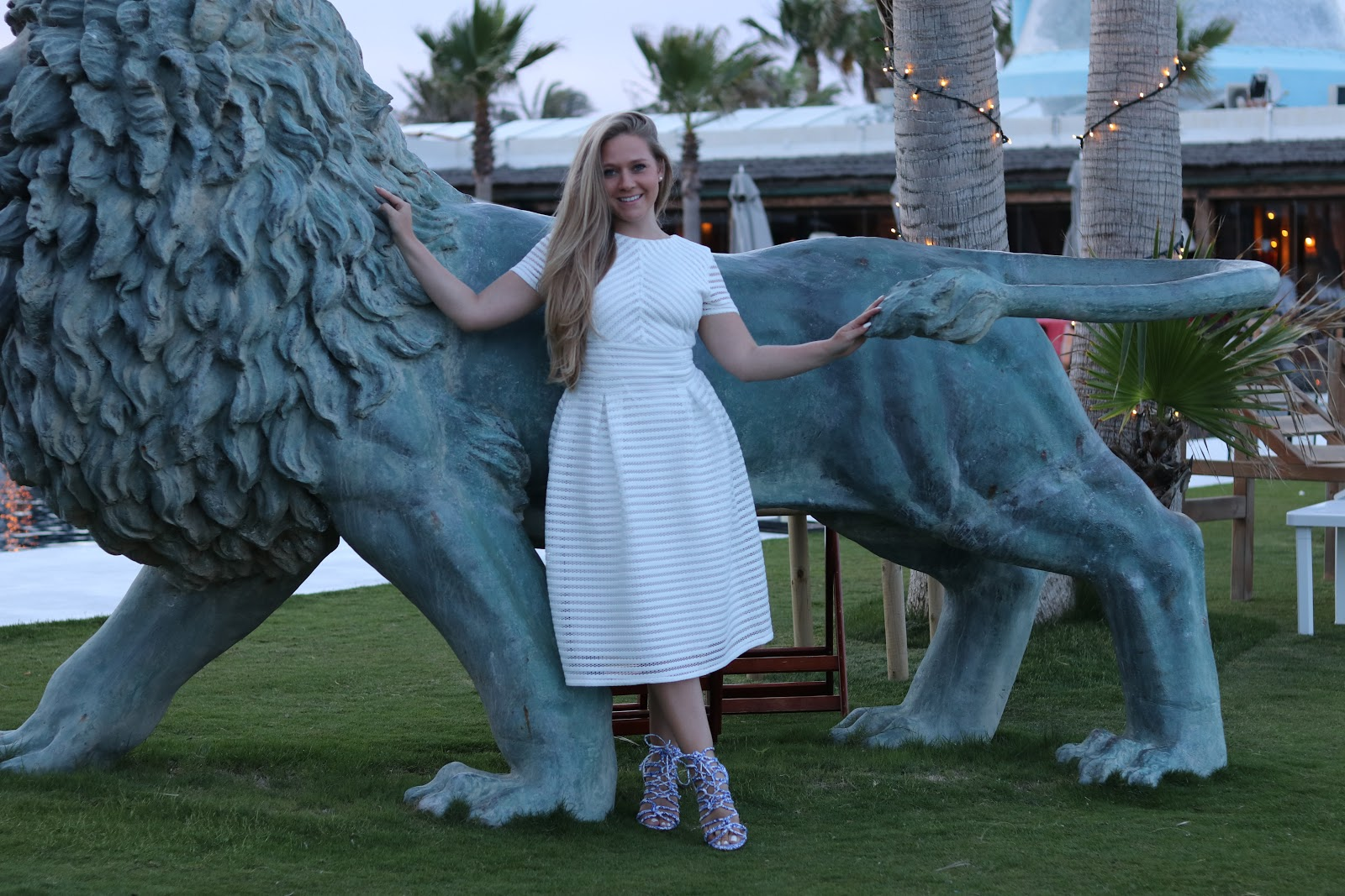 Katie Heath wearing a Boohoo dress leaning against a lion at Trocadero in Sotogrande, Spain
