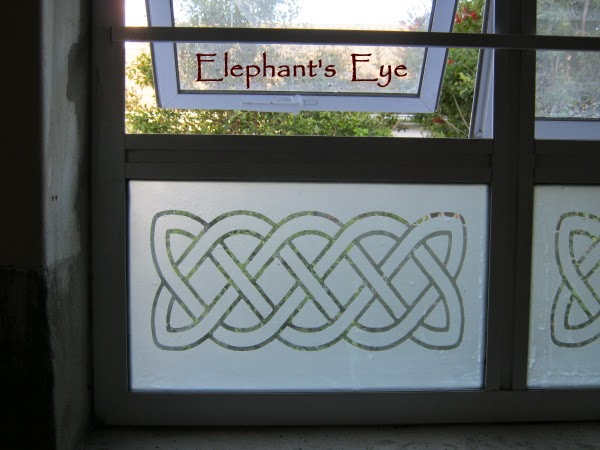 Celtic knot sandblasted across the bottom pane of the bathroom windows
