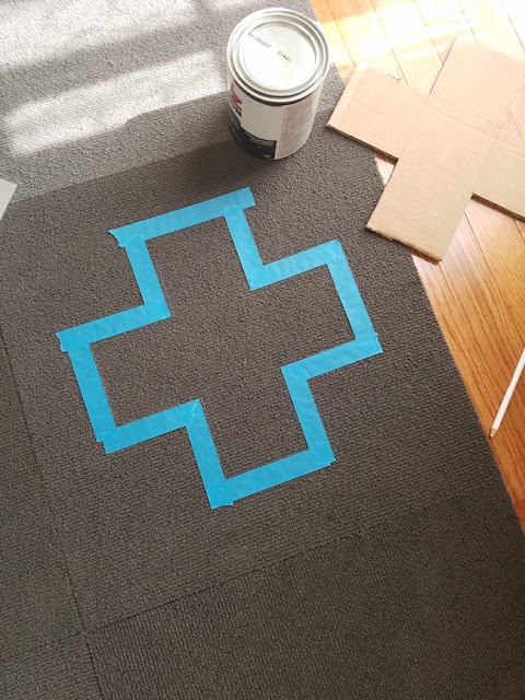 cross area on rug taped with blue tape