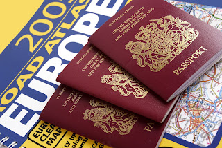 Pic of 3 British Passports on top of  Europe Road Atlas