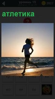 Девушка бежит по берегу, занимаясь легкой атлетикой на фоне прибрежной волны