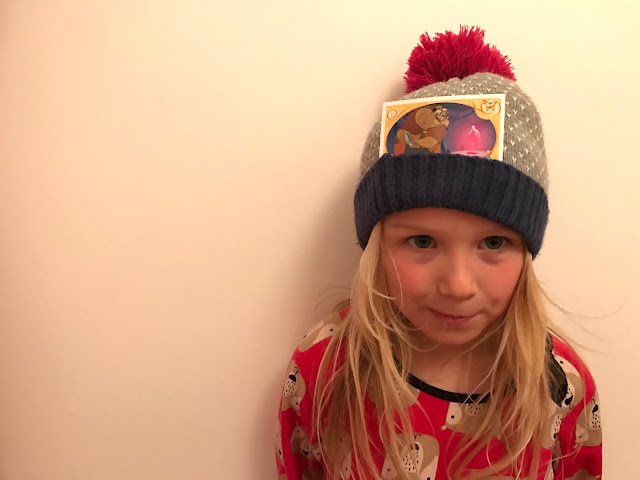 A reluctant child posing with a woolly hat on and a beast card in the folded up flap at the bottom