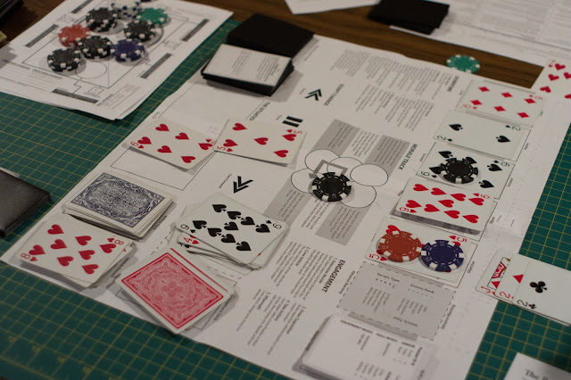 A table with assorted playing components, dice and playing cards, and play sheets and mats.