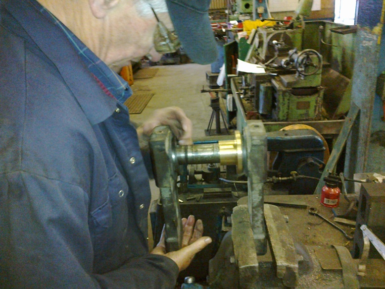 Brian surveys the machining and bushing required for the track idler wheel
