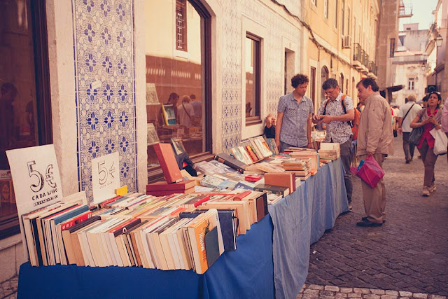 Tourists buying some books at an outdoor book stall in Lisbon, Portual