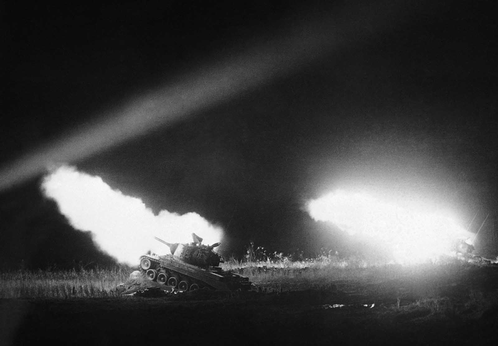Tanks of the 1st Marine Tank Battalion bark death and devastation into the briefly day-lighted Korean night, as Marines fire a night mission at supply installations somewhere in Korea on January 16, 1952.