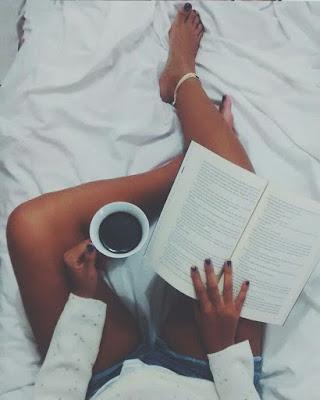 pose acostada en la cama leyendo libro con taza de cafe
