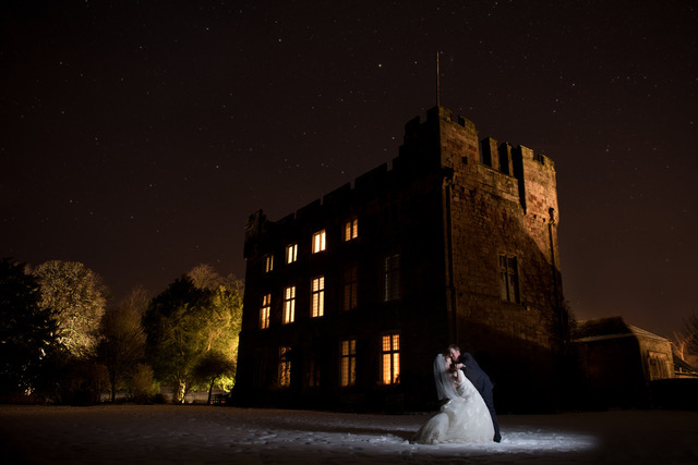 Groom dips bride at night infront of Askham Hall on a snowy lawn