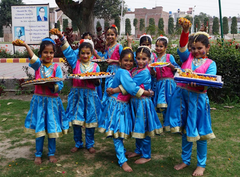 Students celebrating Holi with flowers at Green Land Convent School