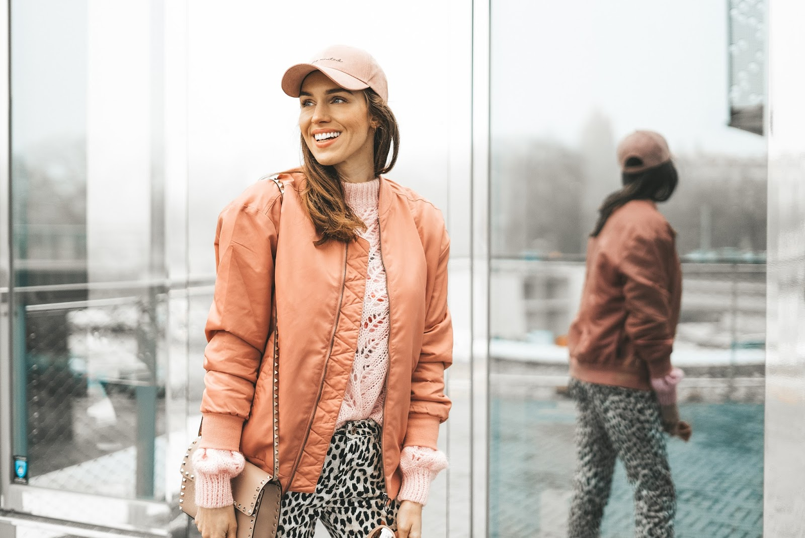 pink cap pink bomber jacket over sweater outfit spring