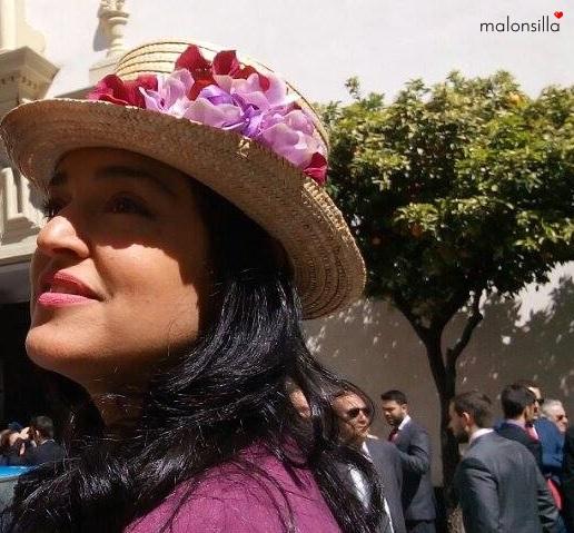 Invitada a boda de invierno con sombrero copa alta tipo chistera de flores en color buganvilla y burdeos, con pelo suelto