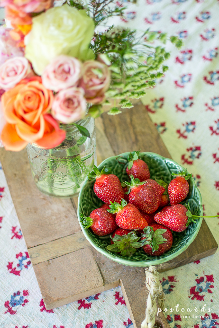 bowl of strawberries and jar of flowers on a wooden cutting board