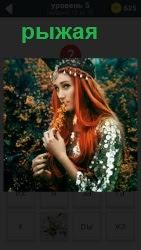 На фоне высоко куста стоит рыжая девушка и в рот рукой осенний листочек направляет