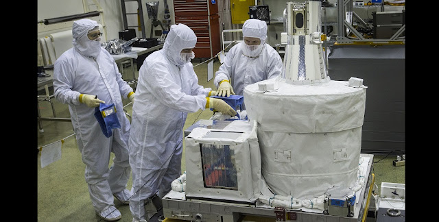Technicians inside a clean room at NASA's Langley Research Center work on the SAGE III instrument, preparing it to ship to NASA's Kennedy Space Center for launch to the International Space Station. The ozone- and aerosol-measuring instrument is the latest in a long line of atmospheric science experiments designed at NASA Langley. Photo Credit: NASA/David C. Bowman