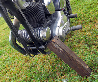 Block of wood serves as kick stand for motorcycle.