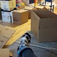 Boîtes de déménagement, salon encombré, jambes croisées