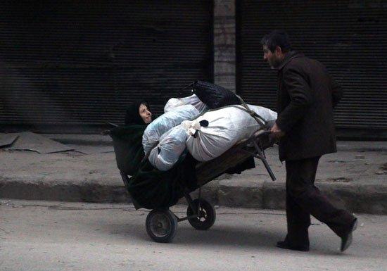 مواطن يحمل سيدة سورية للعودة الي المناطق المحررة من الإرهاب