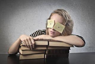 Joven apoyada sobre una pila de libros, con los ojos cerrados y dos papeles sobre los párpados donde se dibujan sus ojos