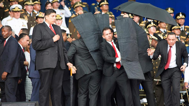 Image Attribute: One of the images posted on social media showed security officers surrounding Maduro with multiple black bullet-proof shields forming a barrier as they escorted him from the attack site. Date: August 4, 2018, / Source: Twitter