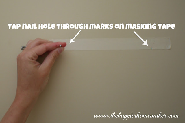 Someone holding masking tape with picture frame marks on it  on a wall to mark where the nails should go and be level