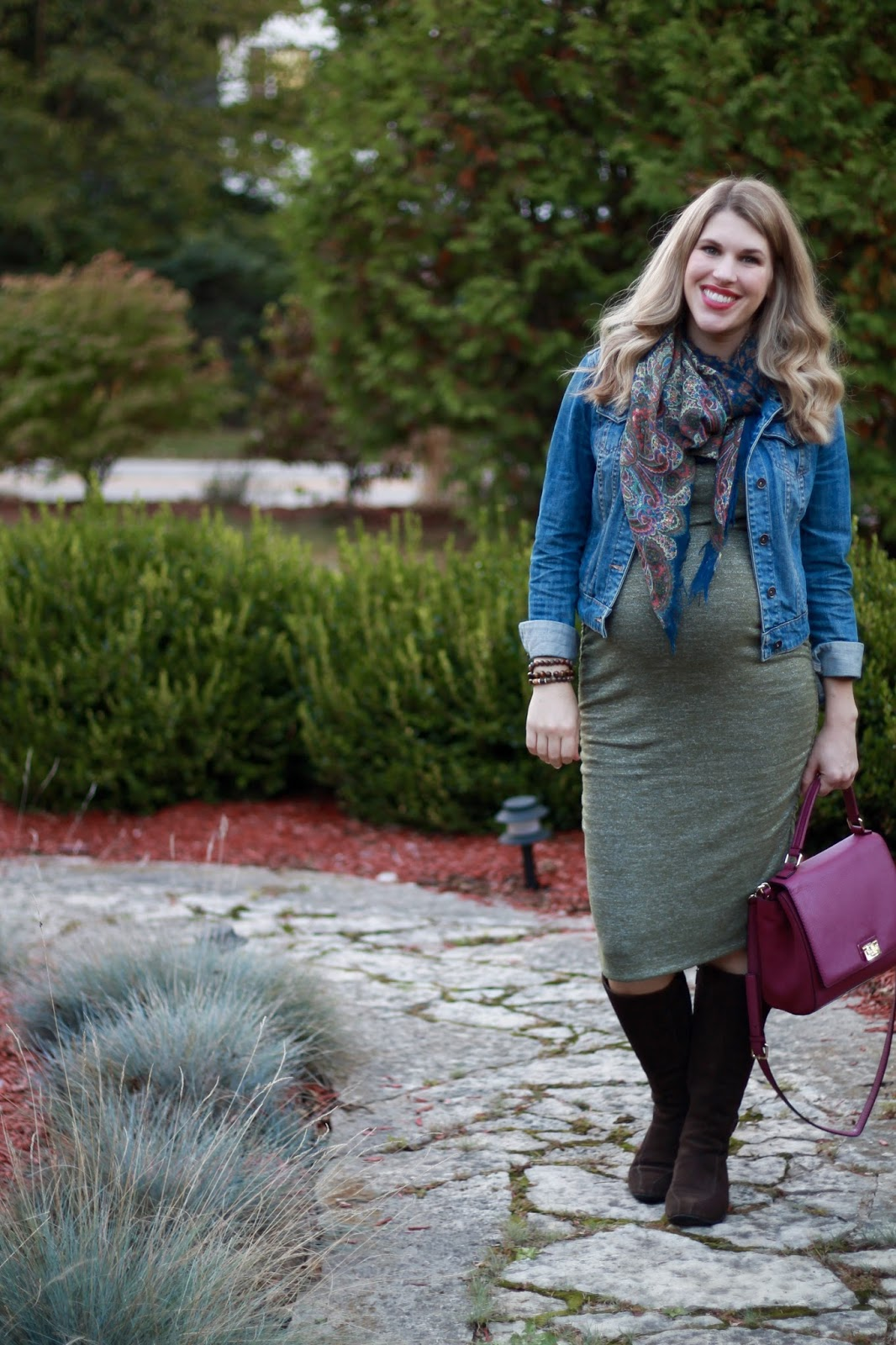 olive maternity dress, denim jacket, navy floral scarf, brown riding boots, berry colored bag