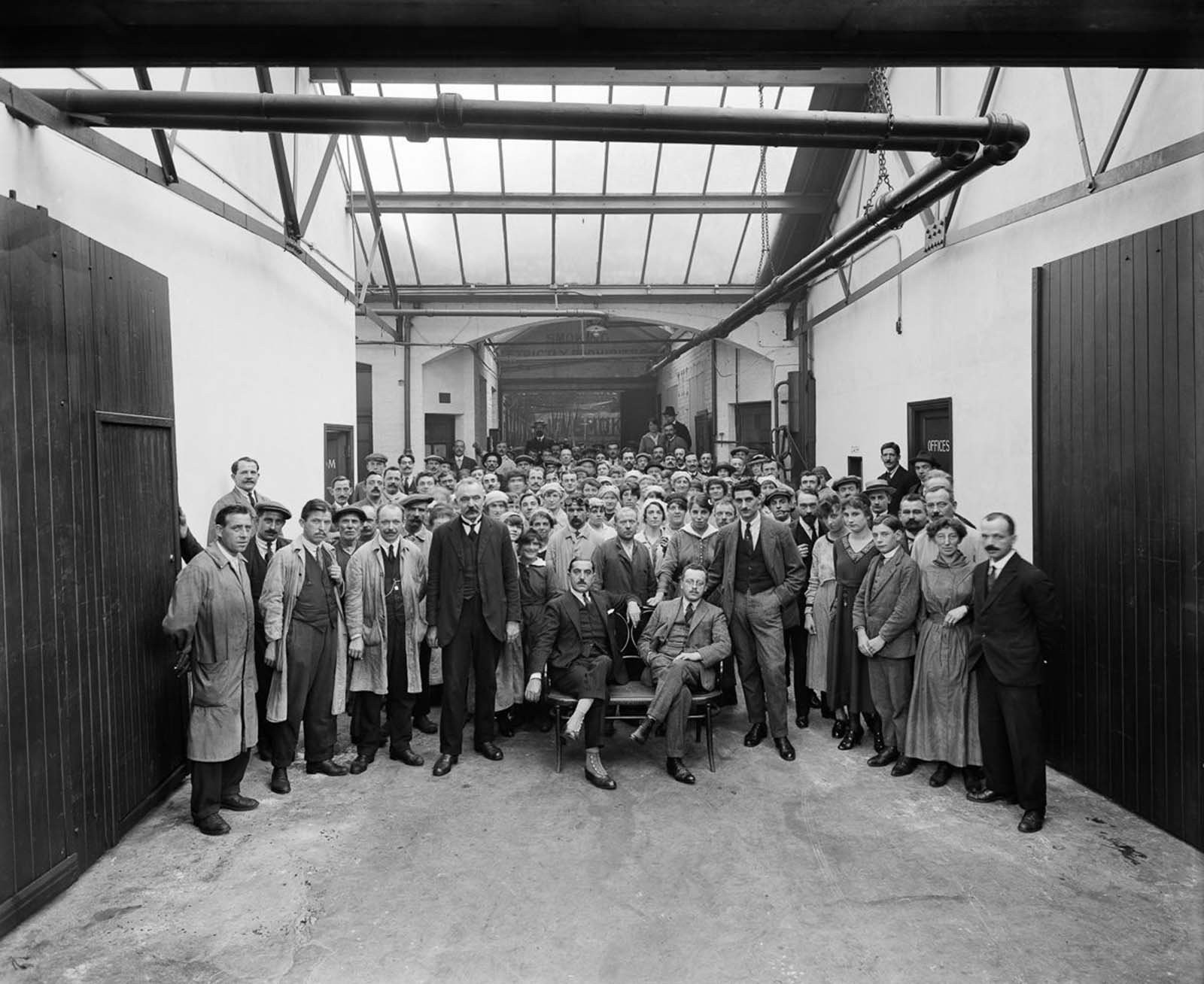 A group portrait of the managers and workers in the Belgian Munition Works in London, which employed Belgian refugees to manufacture grenades and artillery shells for the war effort. 1918.