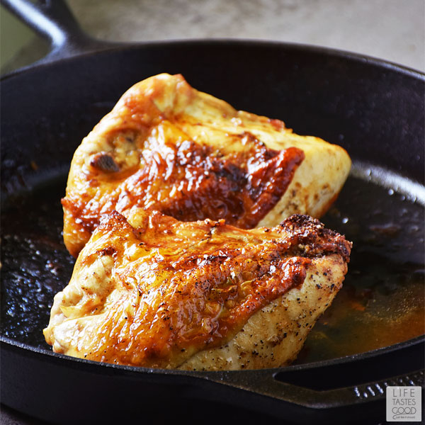 Looking straight on at cast iron skillet with pan roasted chicken Breasts ready to eat