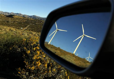 wind turbines reflected in a car mirror