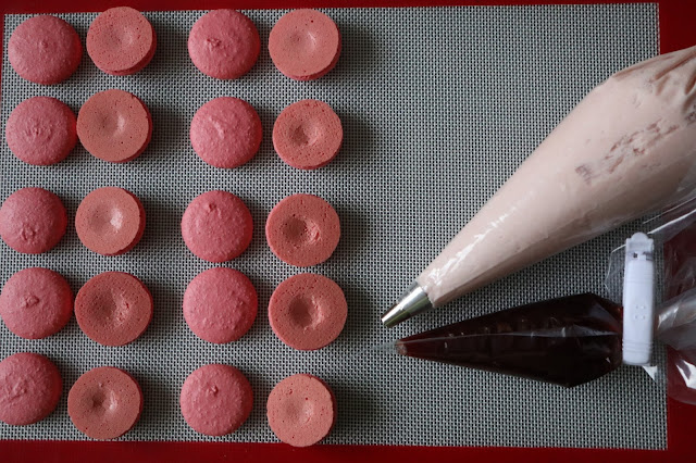 Macarons about to be filled with strawberry buttercream and jam